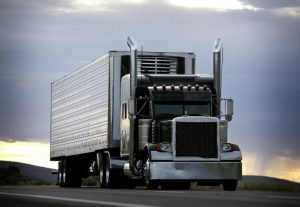 Global Locator Systems | Semi driving on highway with sun setting in background